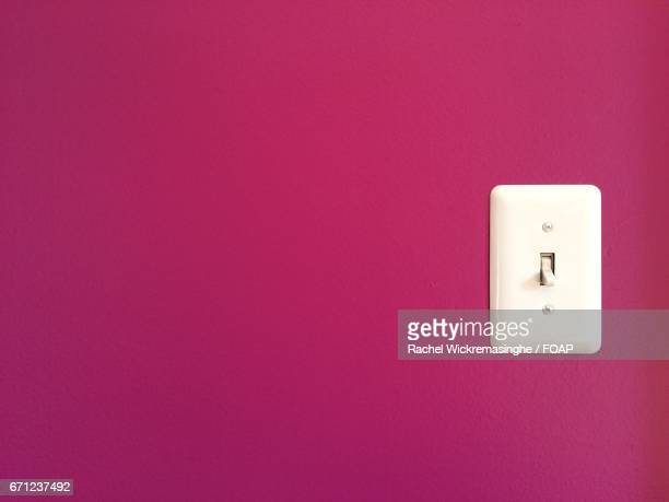 Close-up of pink wall and light switch