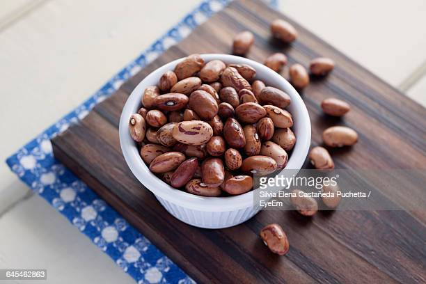 close-up of pinto beans in bowl on cutting board - pinto bean stock photos and pictures