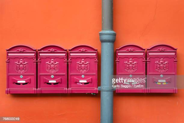 close-up of pipe and mailboxes on orange wall - pink tube photos et images de collection