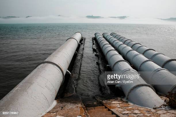 Close-Up Of Pipes By Sea Against Sky