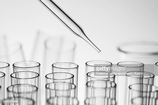 close-up of pipette and test tube against white background - pipette stock pictures, royalty-free photos & images