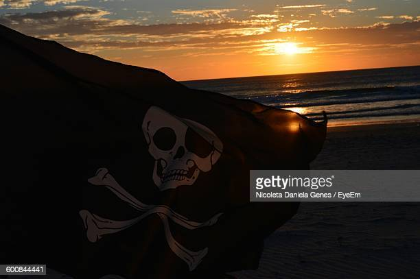 Close-Up Of Pirate Flag On Beach By Sea During Sunset