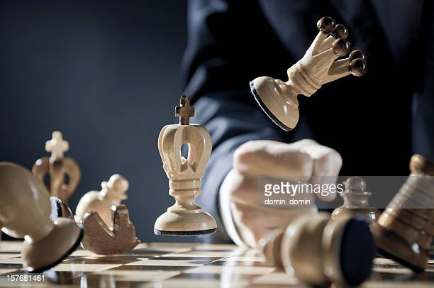 Close-up of pissed off chess player punches in the chessboard