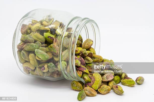 Close-Up Of Pistachio Nuts In Jar On White Background