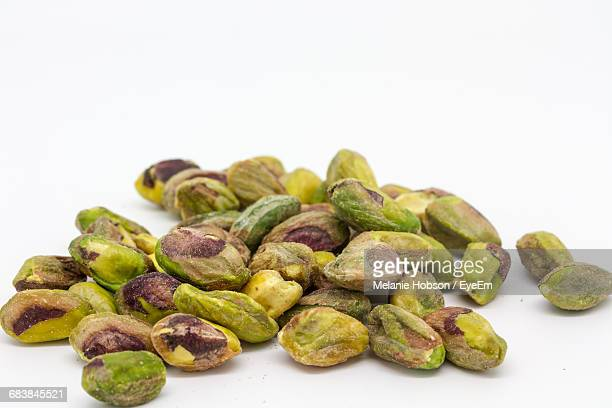 Close-Up Of Pistachio Nuts On White Background