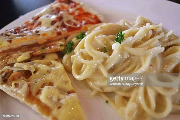 Close-Up Of Pizza Slices With Noodles In Plate