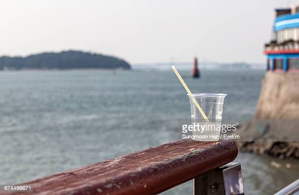 Close-Up Of Plastic Cup With Cold Beverage On Wooden Railing