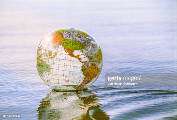 close-up of plastic globe floating on water - physical geography stock pictures, royalty-free photos & images