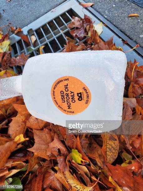 Close-up of plastic waste motor oil collection container, washed into a storm drain during a rain storm, San Ramon, California, December 8, 2019.