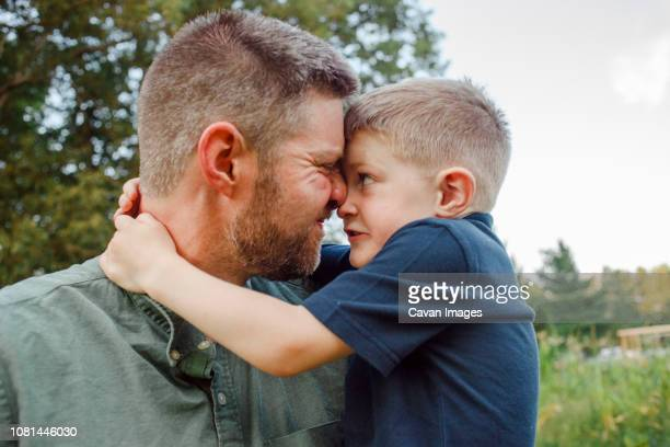 Close-up of playful father and son embracing while standing in forest