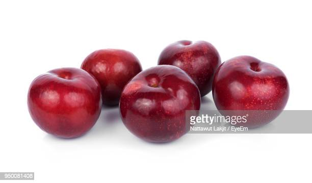 Close-Up Of Plums Against White Background