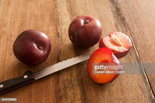 Close-Up Of Plums With Knife On Wooden Table