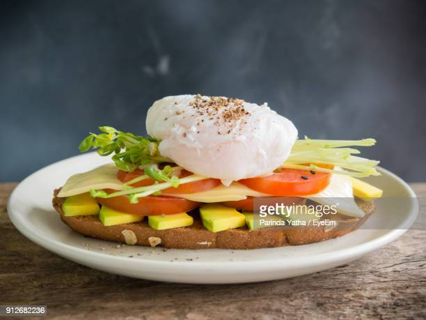 close-up of poached egg with open sandwich in plate - avocado toast stockfoto's en -beelden