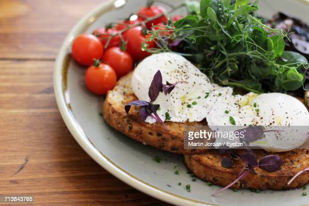 Close-Up Of Poached Eggs On Toasted Bread With Herbs And Cherry Tomatoes In Plate