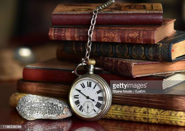 close-up of pocket watch against old books on table - 歴史 ストックフォトと画像