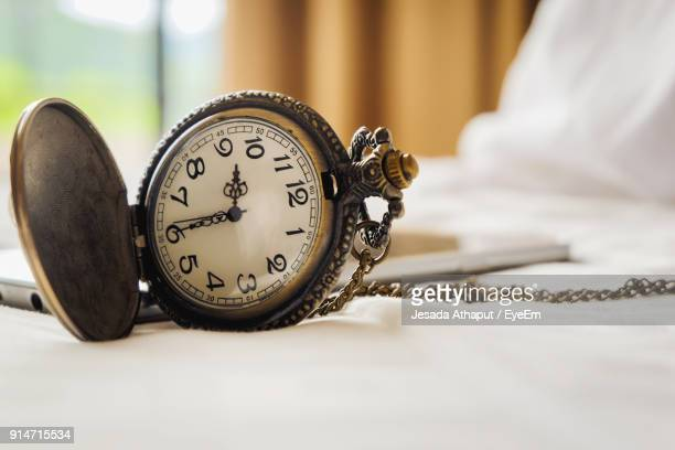 Close-Up Of Pocket Watch On Bed