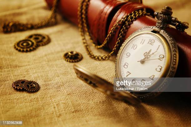 close-up of pocket watch on table - antique stock pictures, royalty-free photos & images