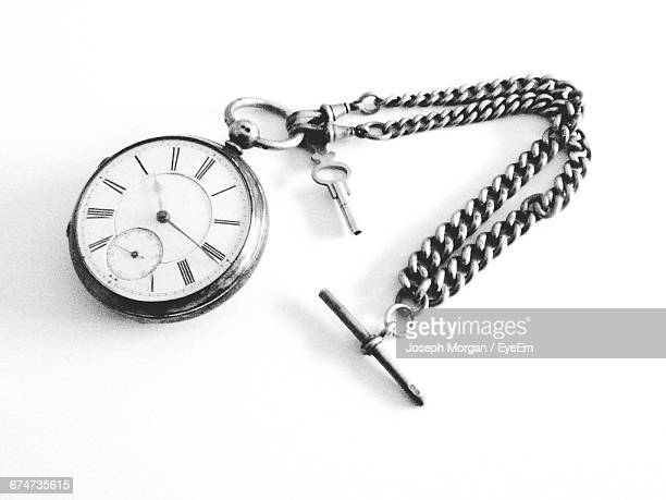 Close-Up Of Pocket Watch On White Surface