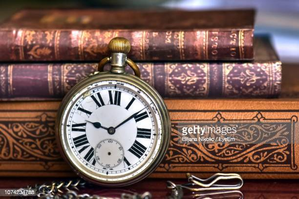 Close-Up Of Pocket Watch With Stacked Books On Table