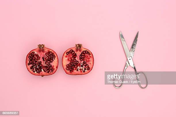 Close-Up Of Pomegranate And Scissor On Pink Background