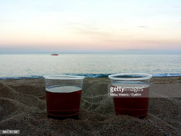 Close-Up Of Pomegranate Juice In Plastic Glasses On Beach