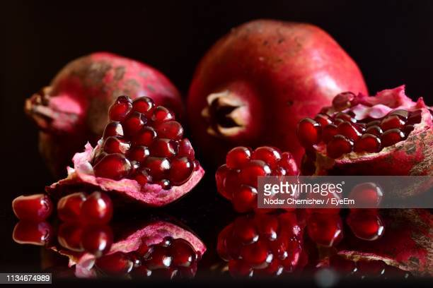 close-up of pomegranate on black background - juicy stock pictures, royalty-free photos & images