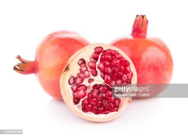 close-up of pomegranate on white background - pomegranate stock pictures, royalty-free photos & images