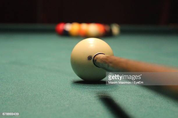 Close-Up Of Pool Cue By Balls On Table