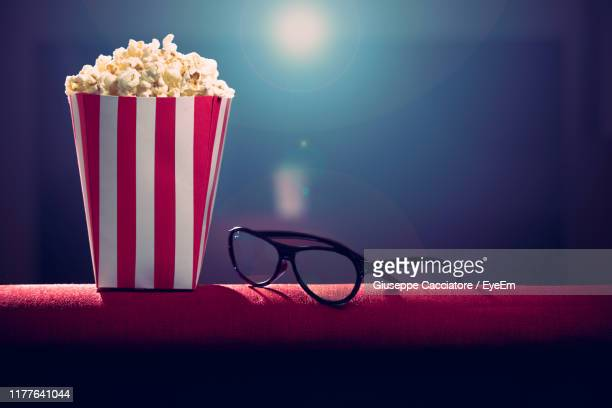 close-up of popcorn and eyeglasses on table - popcorn stock pictures, royalty-free photos & images