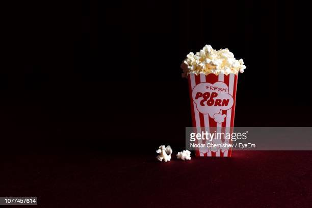 close-up of popcorns against black background - popcorn stock pictures, royalty-free photos & images