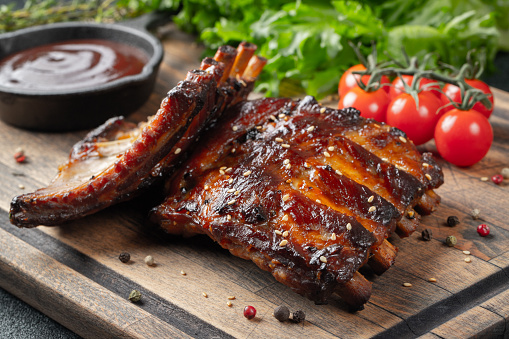 Closeup of pork ribs grilled with BBQ sauce and caramelized in honey. Tasty snack to beer on a wooden Board for filing on dark concrete background 1086140442