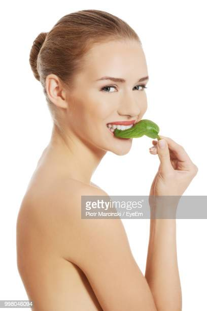 Close-Up Of Portrait Smiling Woman Eating Leaf Vegetable Against White Background