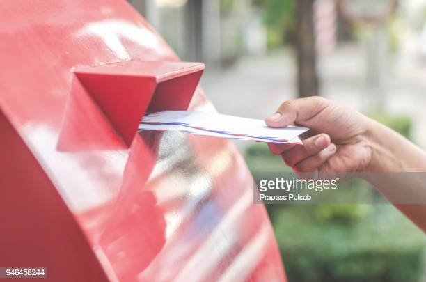 close-up of postman putting letters in mailbox - sending stock photos and pictures