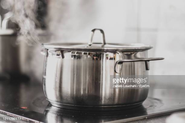 close-up of pot with steam on stove at home - saucepan stock pictures, royalty-free photos & images