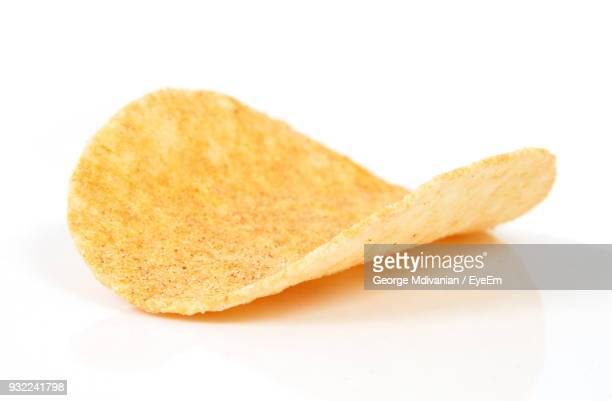 close-up of potato chip against white background - ポテトチップス ストックフォトと画像