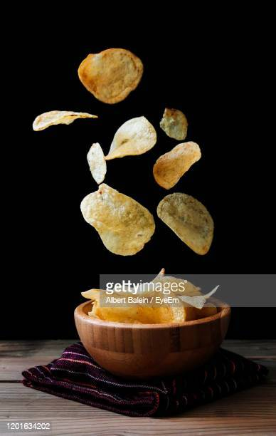 close-up of potato chips falling in bowl against black background - ポテトチップス ストックフォトと画像