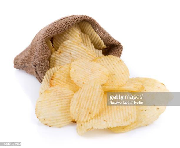 Close-Up Of Potato Chips In Bowl Against White Background