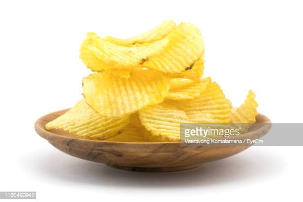 close-up of potato chips in bowl against white background - ポテトチップス ストックフォトと画像
