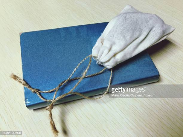 Close-Up Of Pouch With Book On Wooden Table