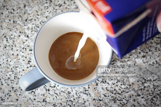 Close-Up Of Pouring Milk In Cup
