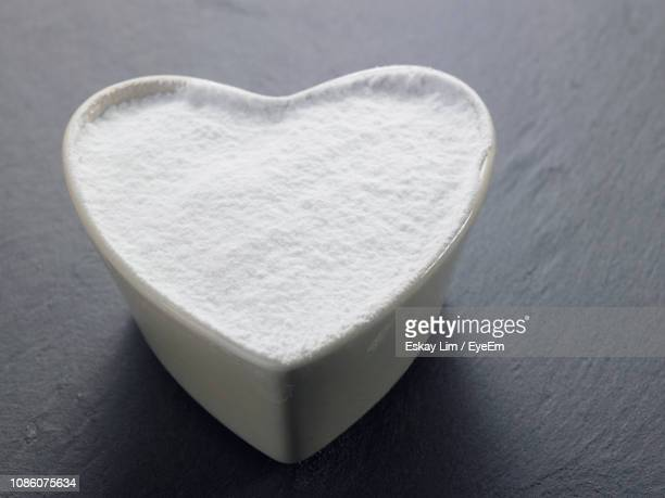 close-up of powdered sugar in heart shape bowl on table - icing sugar stock pictures, royalty-free photos & images