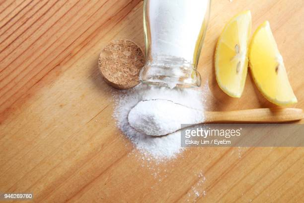 Close-Up Of Powdered Sugar In Wooden Spoon With Lemon Slices On Table