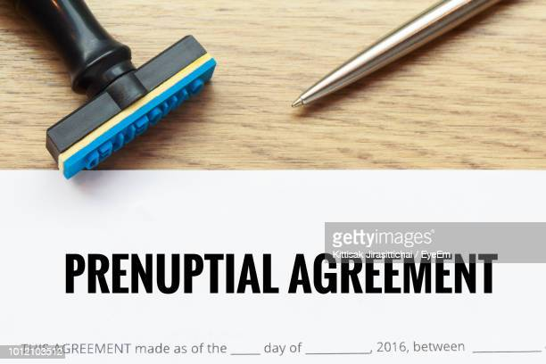 Close Up Of Prenuptial Agreement And Rubber Stamp On Table