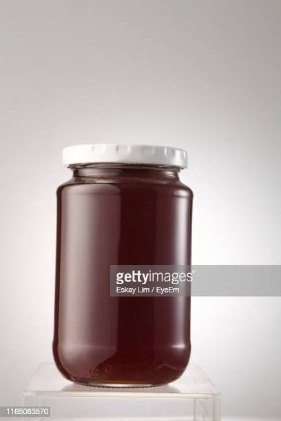 close-up of preserves jar on table against gray background - jar stock pictures, royalty-free photos & images