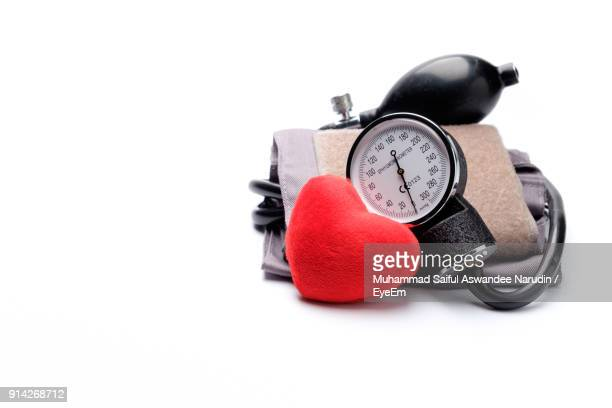 close-up of pressure gauge with red heart shape against white background - pressure gauge stock photos and pictures