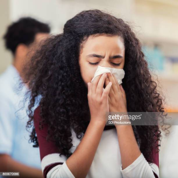 closeup of preteen girl sneezing into a tissue - cough stock photos and pictures