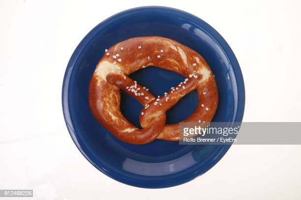 Close-Up Of Pretzel In Plate Over White Background