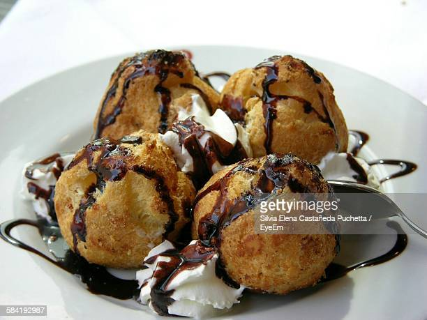 Close-Up Of Profiteroles Filled With Ice Cream On Plate