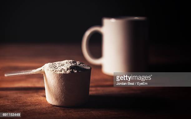 Close-Up Of Protein Powder In Scoop With Cup On Wooden Table