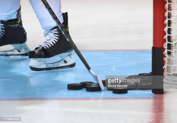 Closeup of pucks, a stick and skates as photographed during warm-ups prior to the game between the New York Islanders and the Philadelphia Flyers at...